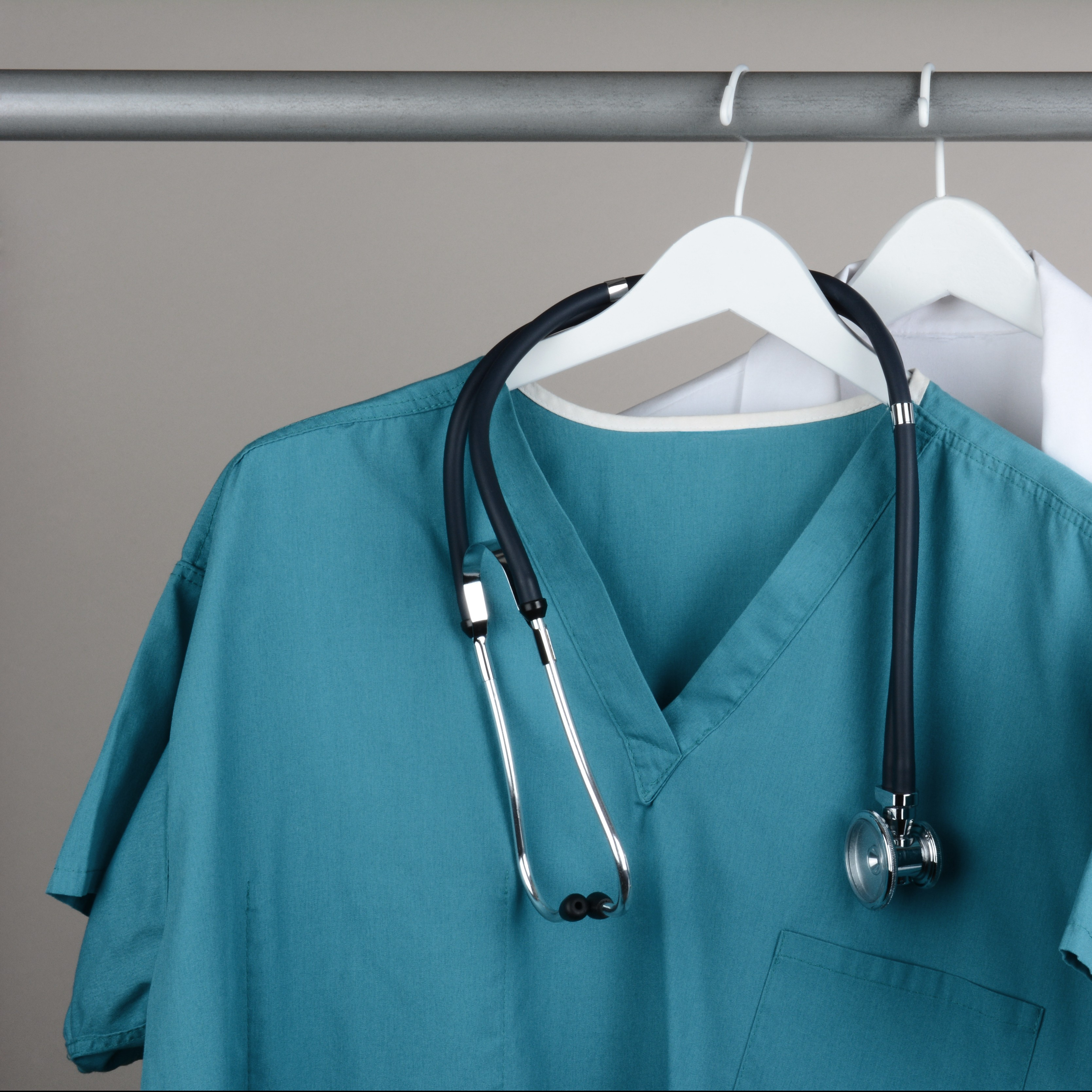 Closeup of a doctor's scrubs with stethoscope and lab coat on ha