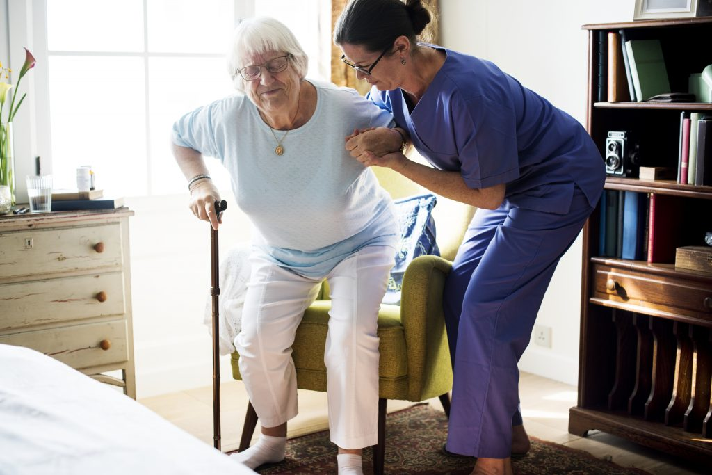 """""""Nurse helping senior woman to stand"""" home and community-based services"""