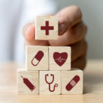 Hand arranging wood block stacking with icon healthcare medical, Insurance