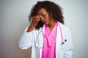 African american doctor woman wearing pink stethoscope over isolated white background tired rubbing nose and eyes feeling fatigue and headache. Stress and frustration concept.