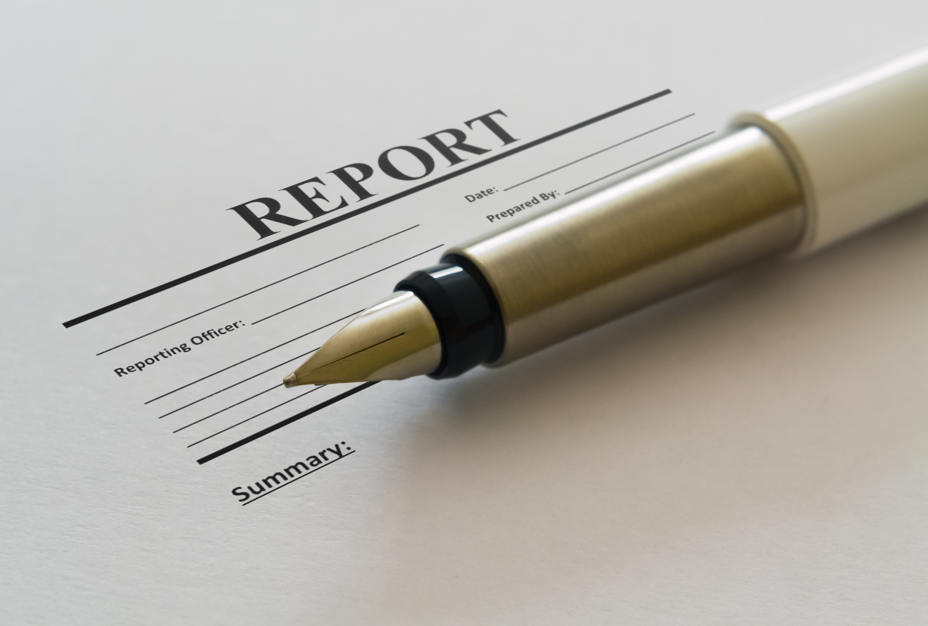 Closeup of a fountain pen and blank report form